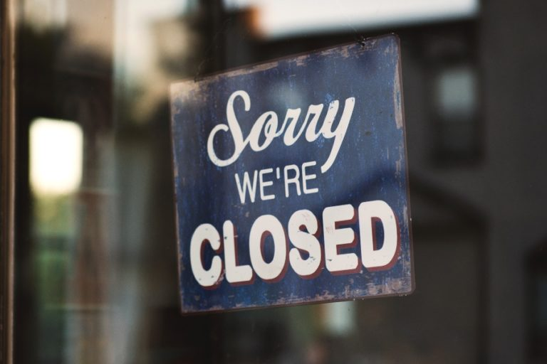 blue sign that reads: Sorry we're closed