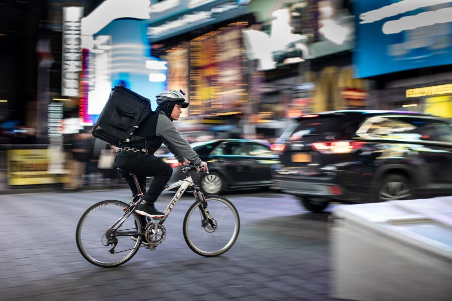 cyclist with food delivery backpack cycling through city