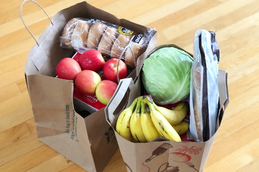 two paper bags of food, including apples, bananas, bagels, cabbage and bread
