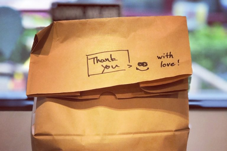 "closed paper bag of food with ""thank you"" and ""with love"" written on it alongside a smiley face"